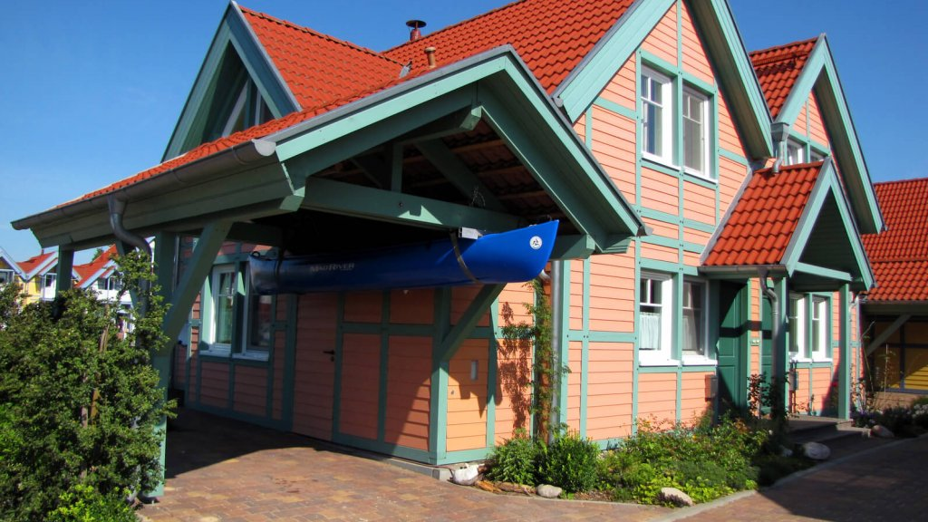 wooden house with carport and boat